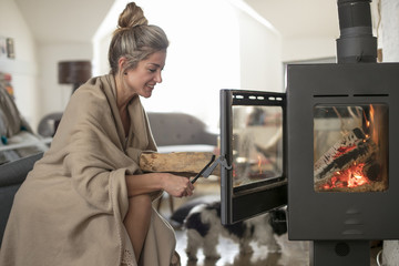 Beautiful middle-aged woman inserts wooden logs into the fireplace. Living room with fire