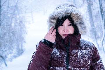 A portrait of an Asian woman in snow storm