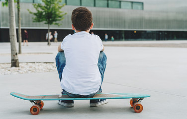 Back view. The boy, dressed in a white T-shirt and blue jeans, sits on a city street on a skateboard. On background modern building in soft focus. Lifestyle. Space for text, logo, image. Mock up.