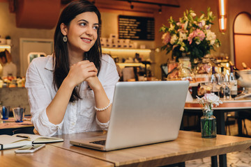 Young businesswoman wearing in shirt sitting in cafe at table, looking at window and smiling. On desk is laptop, notebook. Freelance,startup.Distance work,learning.Online marketing,education.Lifestyle