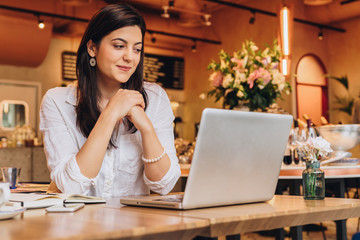 Young businesswoman wearing in shirt sitting in cafe at table, looking on screen of computer and smiling. Freelance, startup. Distance work, learning, blogging. Online marketing, education. Lifestyle.