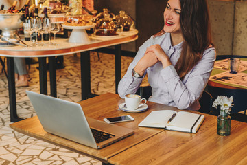Young businesswoman wearing in shirt sitting in cafe at table and laughing. On desk is laptop, notebook, smartphone. Freelance, startup. Distance work, learning. Online marketing, education. Lifestyle