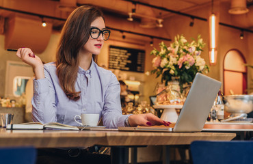 Young businesswoman is sitting in cafe at table, working on laptop. Hipster girl blogging, browsing internet, learning online, checking email.Online marketing,education, e-learning.Freelance, startup.