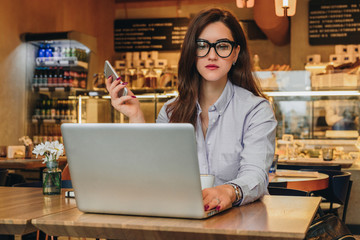 Front view. Young businesswoman is sitting in cafe at table, working on laptop. Hipster girl blogging, browsing internet, learning online, checking email. Online marketing, education, e-learning.