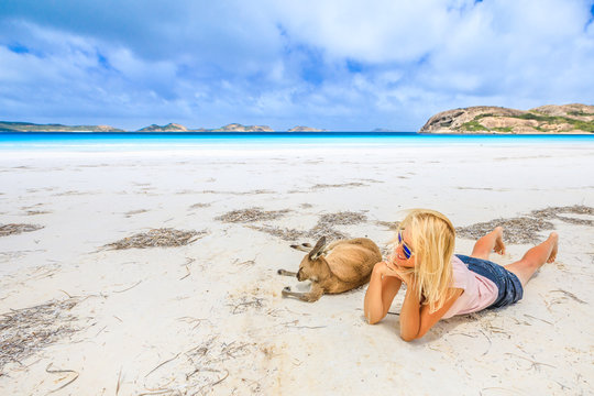 Happy woman lying on pristine white sand of Lucky Bay near Kangaroo. Cape Le Grand National Park, Esperance, Western Australia. Female tourist enjoys one of the most paradisiacal Australian beaches.