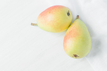 Couple of Ripe Organic Pears in Pastel Green Yellow Red Colors on White Wood and Linen Fabric. Elegant Minimalist Japanese Style. Creative Image for Social Media Blog Product Branding. Copy Space