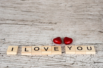 i love you letters and two hearts on white rustic wooden table