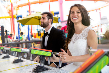 Bride and groom having fun at amusement park theme destination wedding