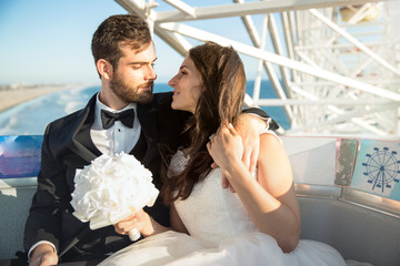 Bride and groom lifestyle alone just married having fun together on ferris wheel at theme park