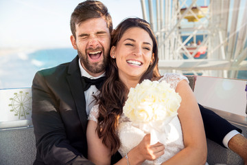 Cute fun bride and groom enjoying honeymoon lifestyle destination wedding on ferris wheel