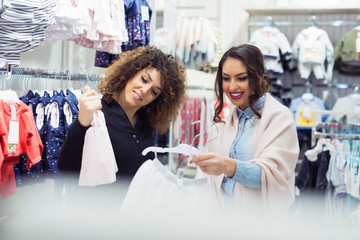 Two cheerful girls shopping for clothes