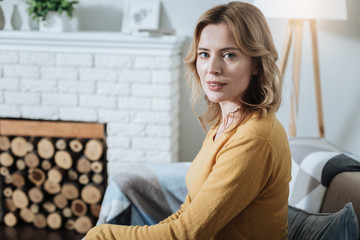Thinking. Beautiful thoughtful blond young woman smiling and sitting on the couch and thinking