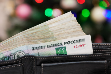 Russian money in the black leather wallet on the multicolored defocused bokeh lights background
