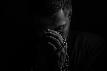 Repented man prisoner with his hands shackled in chains on a dark background