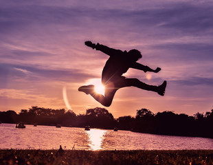 One man is jumping in the air, he is very happy in life with sunset as background.Silhouette image