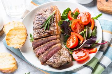 Grilled beef striploin steak with fresh salad.