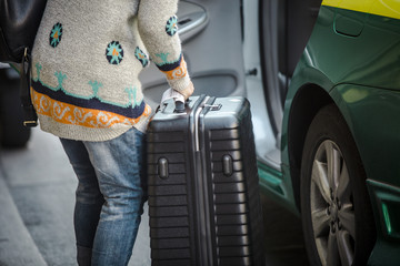Woman packing her suitcase into Taxi cab.