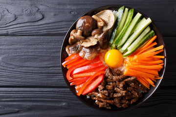Korean cuisine: Bibimbap with beef, raw yolk, vegetables and rice. horizontal top view