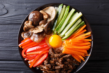 Korean healthy food Bibimbap of rice with fried beef, raw egg, vegetables, shiitake close-up in a bowl. Horizontal top view