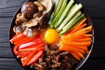 Delicious Bibimbap with beef, egg, vegetables, shiitake and rice close-up in a bowl. horizontal top view