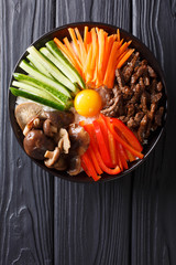 Korean cuisine: Bibimbap with beef, raw yolk, vegetables and rice macro. Vertical top view