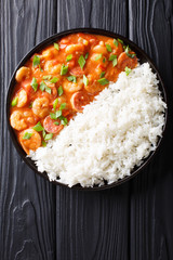 Delicious gumbo with prawns, sausage and rice macro on a plate. Vertical top view