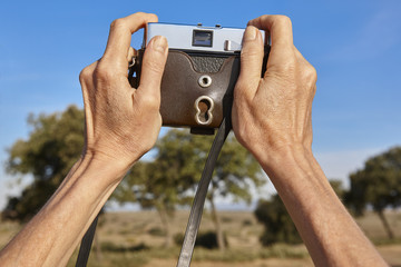 Woman hands holding a film vintage camera in the countryside