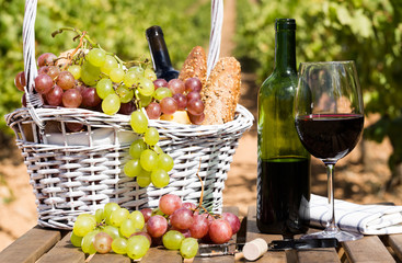 still life with glass of red wine grapes and picnic basket on table Fototapete