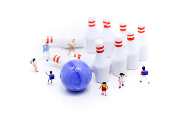 Miniature people : children and student  with Group of Bowling Pins,education and sport concept.
