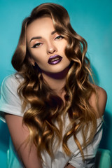 Young sexy girl with perfect curly hairstyle and gloss magenta lips looking at the camera in studio