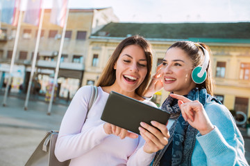Two young beautiful happy women  smiling ,talking and looking something on digital tablet.