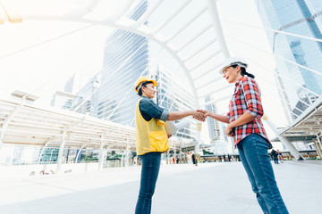Engineers two woman shaking hands working on plan building construction in city