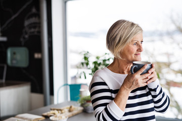 Senior woman holding a cup of coffee in the kitchen.