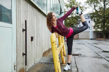 Junge Frau beim Stretching auf einem Bein
