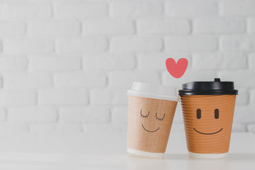 Two coffee cup with smiling face of man and woman together with heart on white brick wall background.Concept of happy Valentines day.