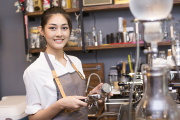 Asian barista woman make a coffee at bar. Woman success to make coffee.