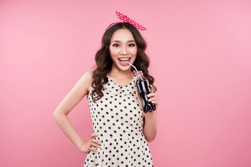 Amazing cute young pretty girl holding soft drink bottle over pink background.