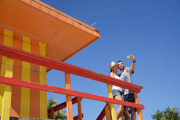 Couple of tourists taking selfie picture on top of Miami lifeguard house