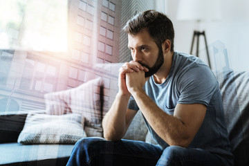 Think about it. Thoughtful serious beardful man sitting in the empty room holding hands near mouth and thinking.