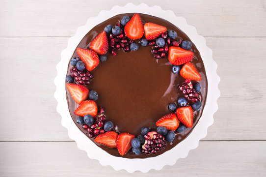 Birthday cake in chocolate with strawberries, blueberries and garnet on white wooden table. Top view. Picture for a menu or a confectionery catalog.