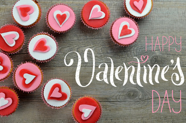 HAPPY VALENTINE'S DAY card with cupcakes decorated with hearts arranged on wooden background