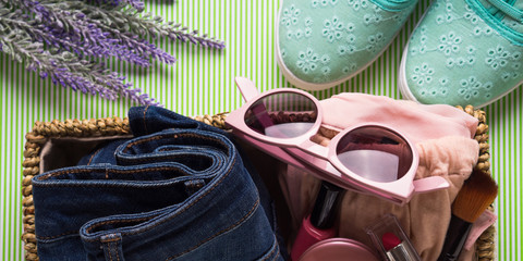 Spring summer Lady's girl's clothes and make up accessories in basket. Seasonal shopping, blog review concept banner
