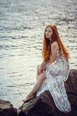 Young red-haired girl in the style of Boho. Enjoys the beauty of the sea coast. The idea and concept of freedom and hippies