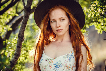 Beautiful red-haired young woman under the shadow of a green tree
