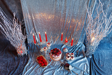 Delicious berry cake, macaroons and muffins on a silver background