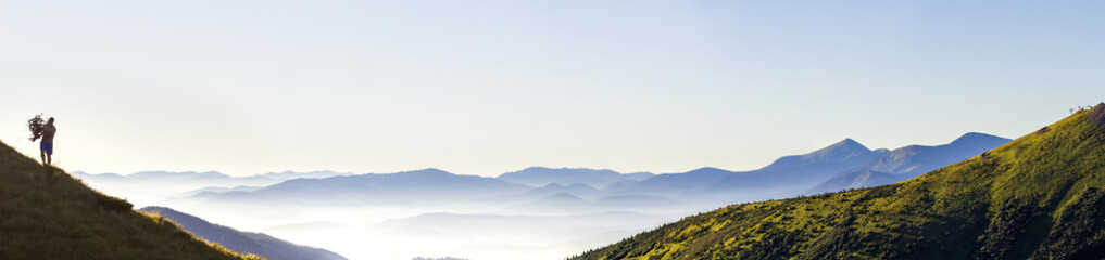 Poster de jardin Alpinisme Wide panorama of morning mountain hills and lonely hiker tourist. Carpathian mountains at sunrise.