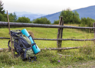 Hikers camping backpack leaning on old wooden fence. Tourist equipment