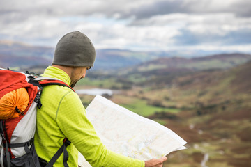 Man explorer looking a map at top of mountain hiking trail Wall mural