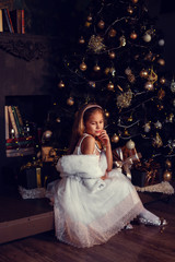A little girl with brown hair on a dark background in cute dress. Gold and black. Christmas Tree and New Year Decorations