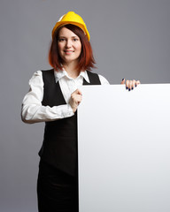 Photo of brunette builder in yellow helmet with sheet of paper
